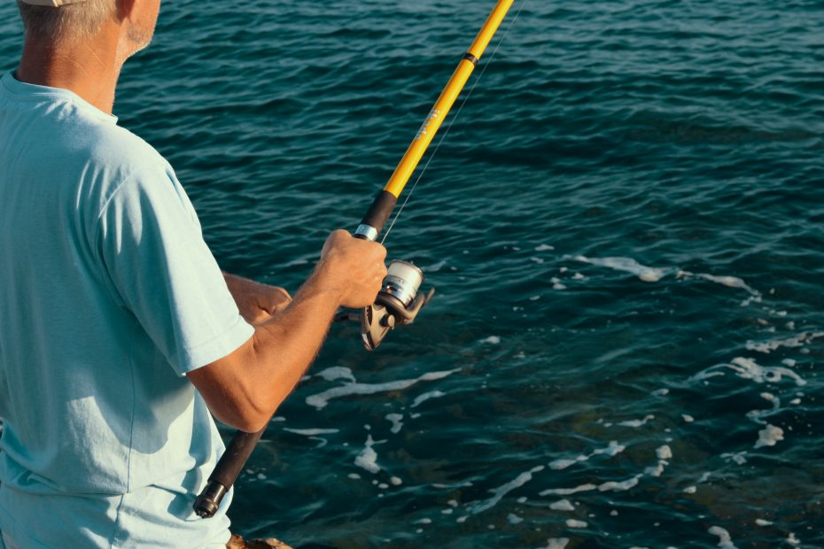selective focus photography of man holding fishing rod