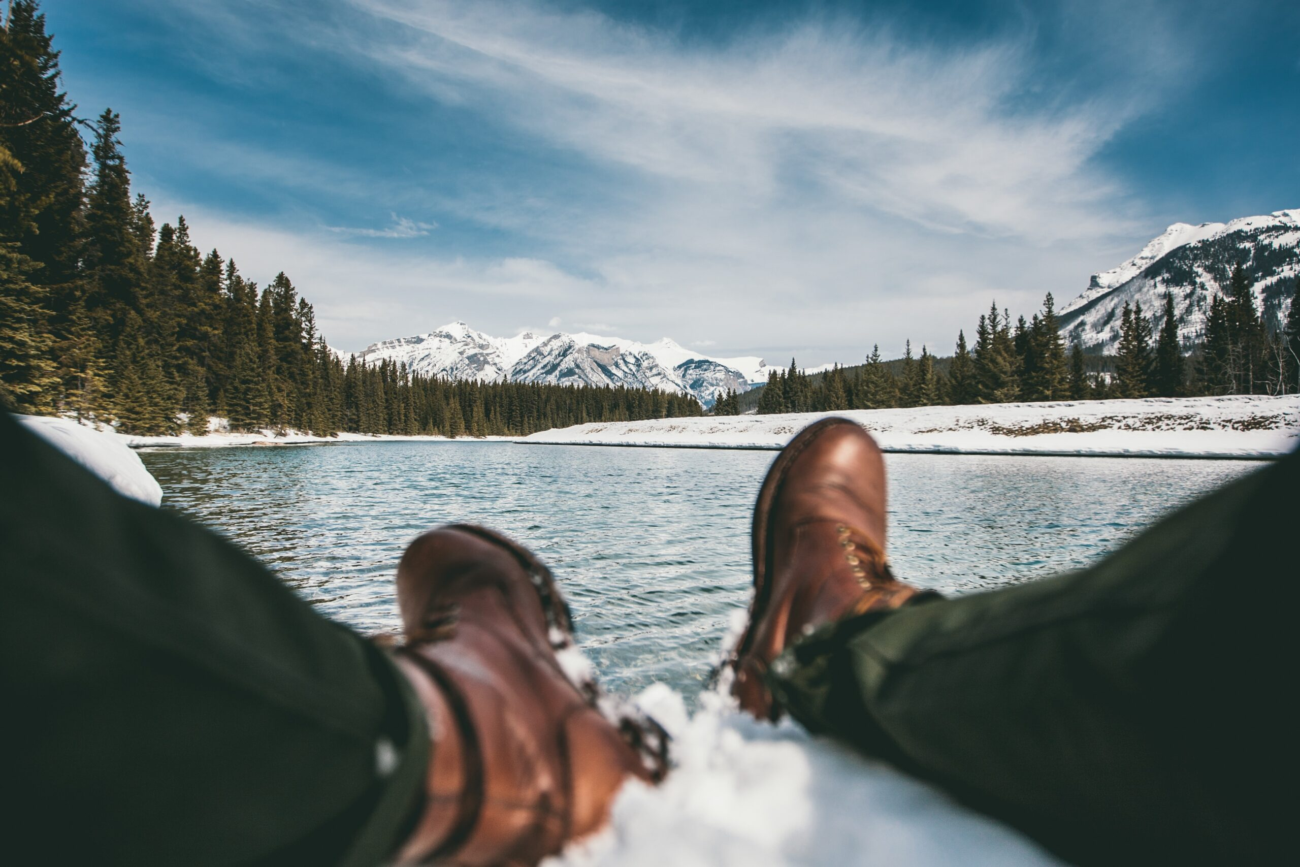 person sitting on snow near body of water