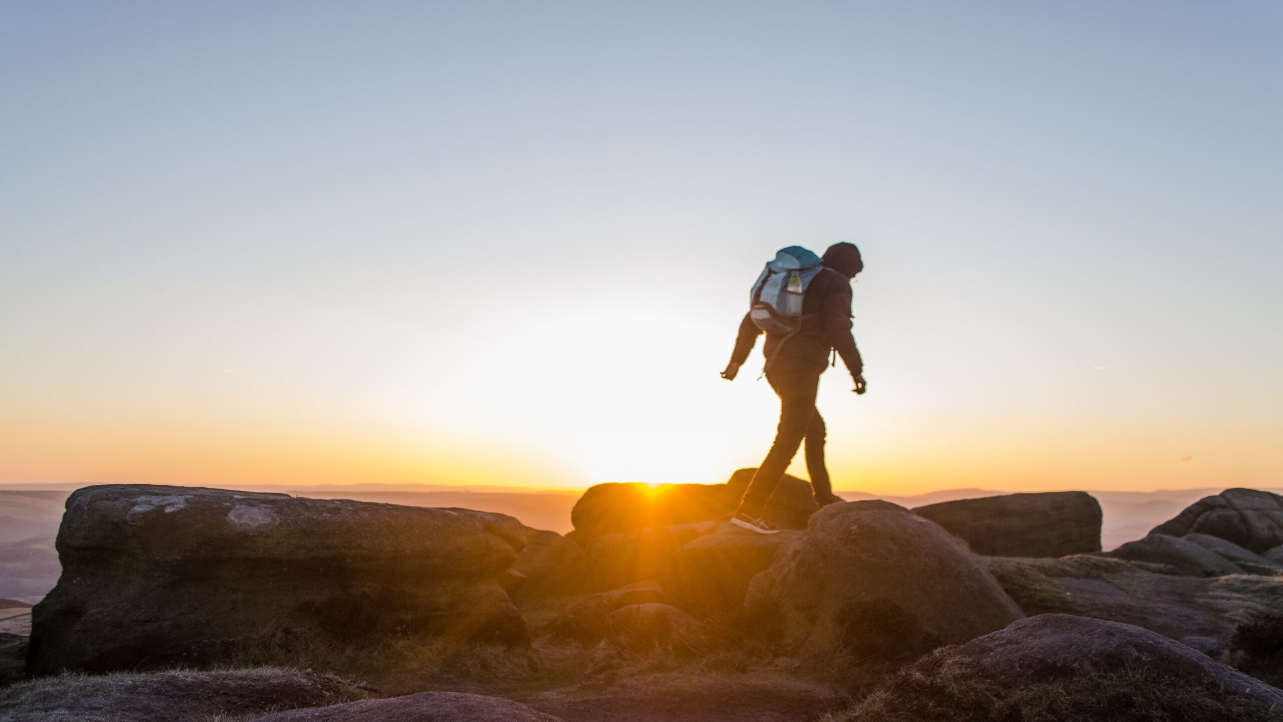 silhouette of man carrying backpack walking on stones